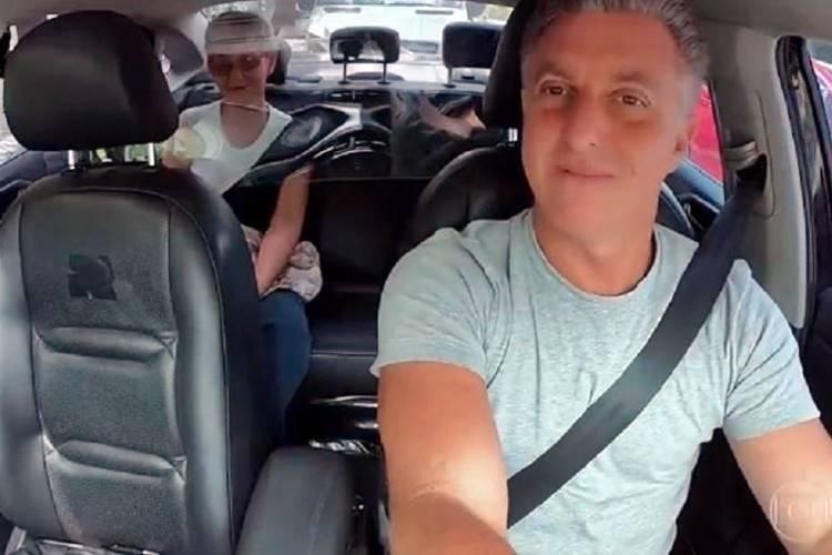 """Luciano Huck causa polêmica ao gravar quadro do """"Caldeirão"""" dentro de táxi sem máscara"""